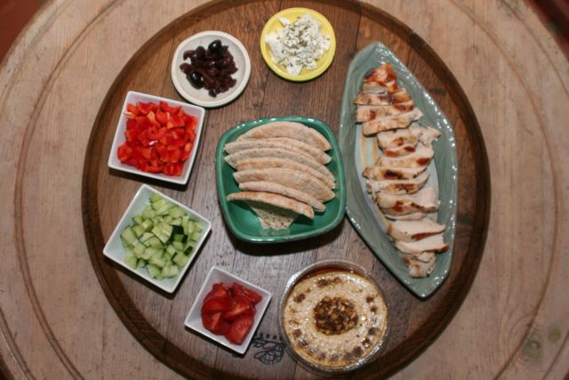 from top and clockwise: feta cheese, grilled lemon chicken, hummus, red bell peppers, cucumbers, tomatoes, kalamata olives, pita triangles (center)